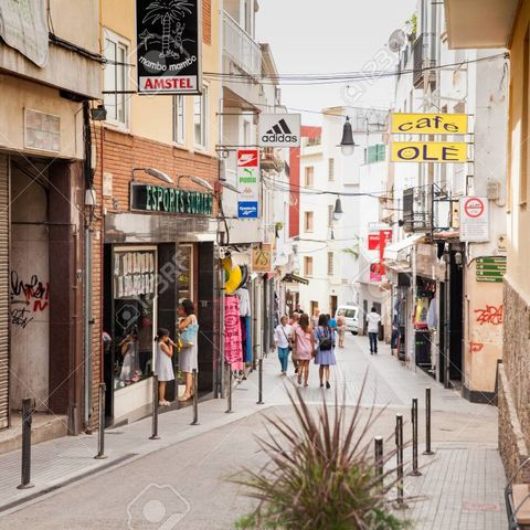 Shops and cafes near the narrow streets of Lloret de Mar. Downtown of Lloret, Spain. Tourists walking the streets of the city.